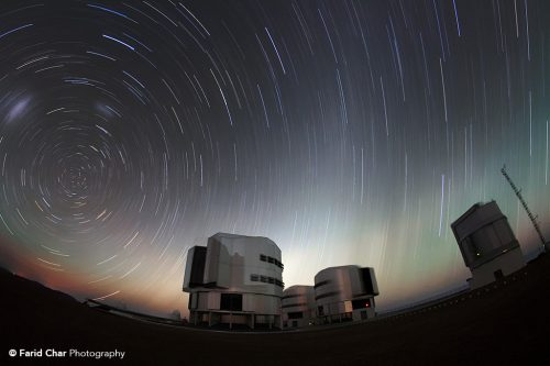 The close of day leaves a band of pale light on the horizon as the stars swing about overhead at Paranal.